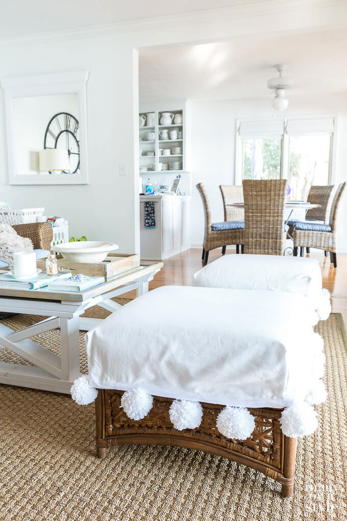 White ottoman covers with large pom-poms.