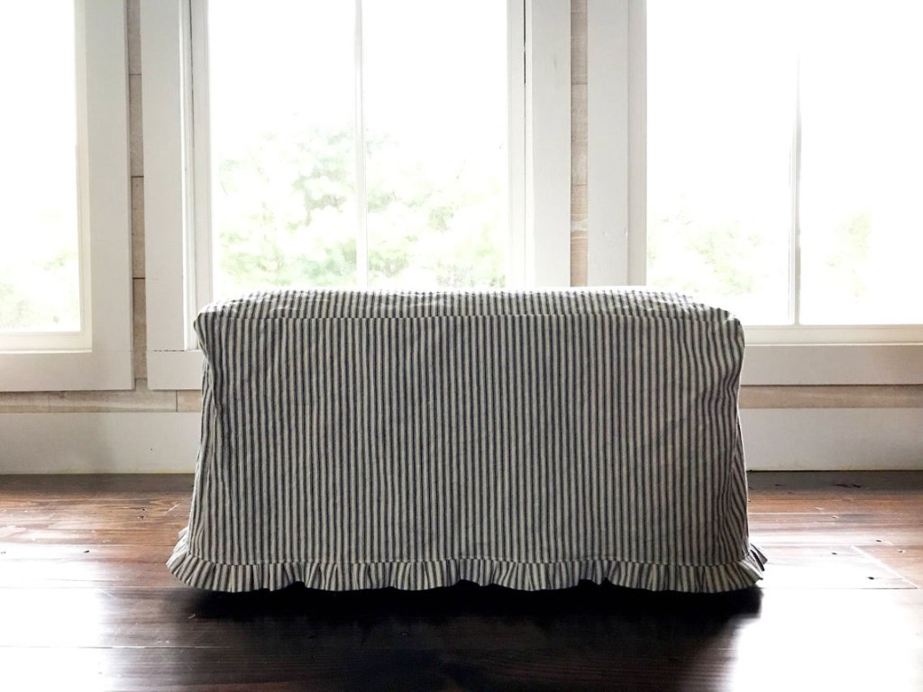 Ticking stripe ottoman slipcover with little ruffle.