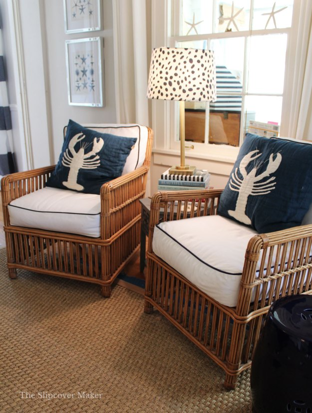Rattan chairs in sunroom with white denim cushions.