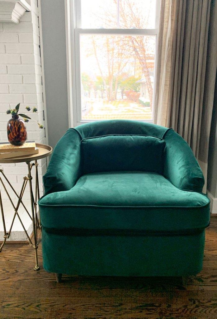 Emerald green velvet chair in front of window.