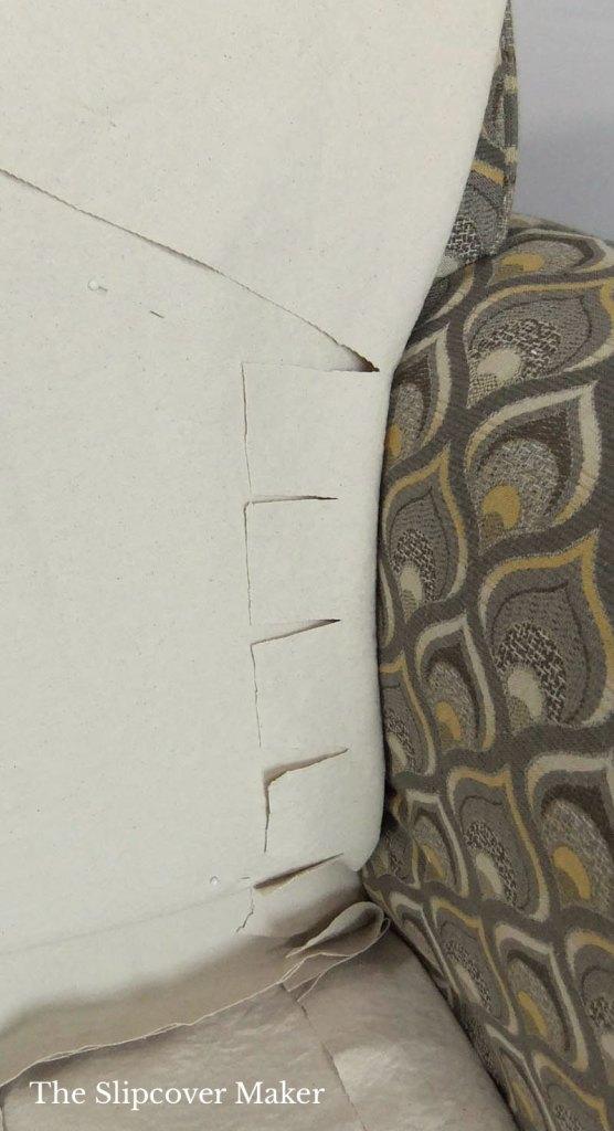 Slipcover cut around inner chair arm.