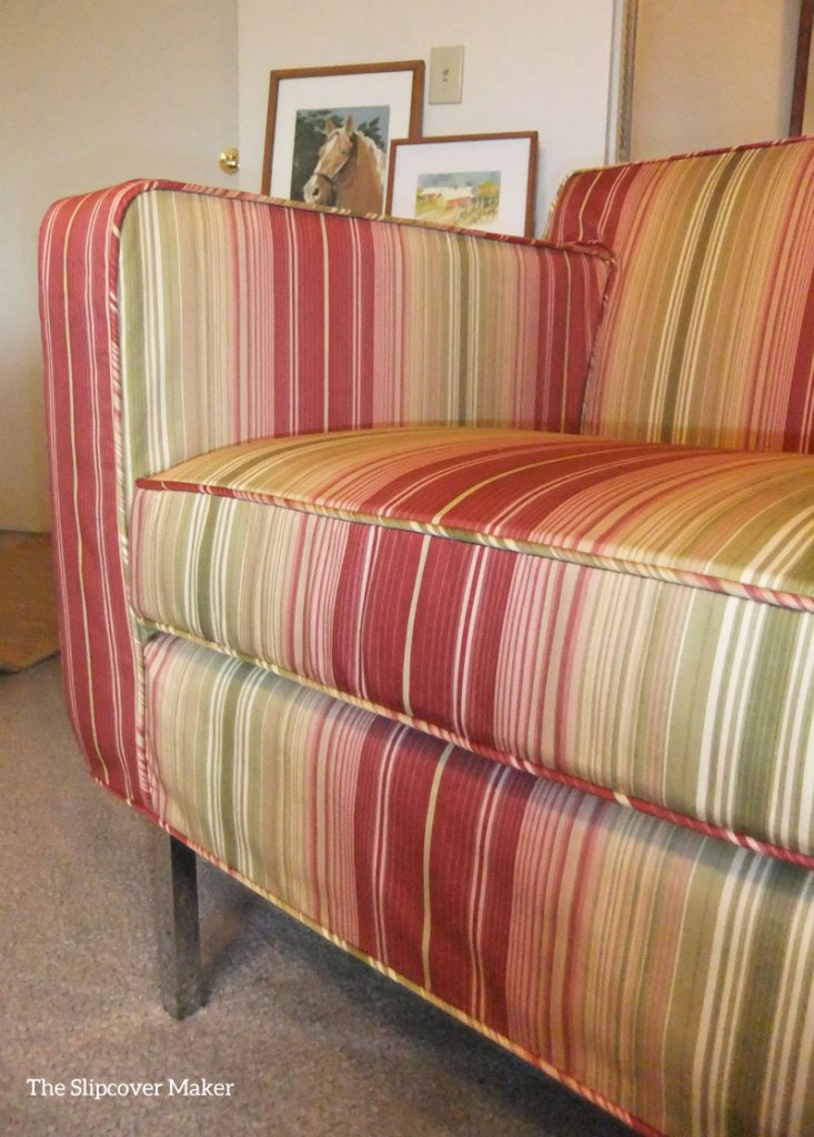 Orange and yellow wide stripe slipcover on chair.