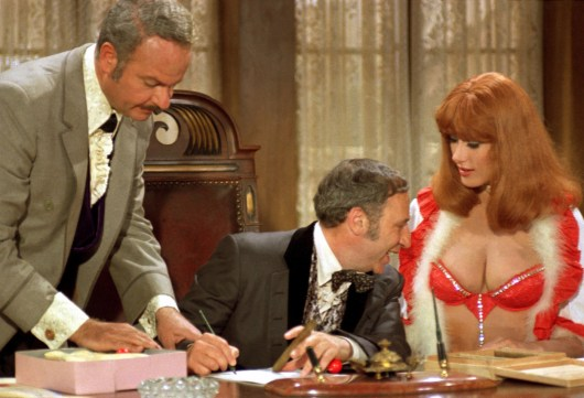 Medium shot of Harvey Korman as Hedley Lamarr, and seated Mel Brooks as Governor Lepetomane staring at chest of Robyn Hilton as Miss Stein.PHOTOGRAPHS TO BE USED SOLELY FOR ADVERTISING, PROMOTION, PUBLICITY OR REVIEWS OF THIS SPECIFIC MOTION PICTURE AND TO REMAIN THE PROPERTY OF THE STUDIO. NOT FOR SALE OR REDISTRIBUTION. ALL RIGHTS RESERVED.