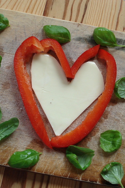 Heart Made Of Paprika And Cheese With Herbs Sprinkled Around