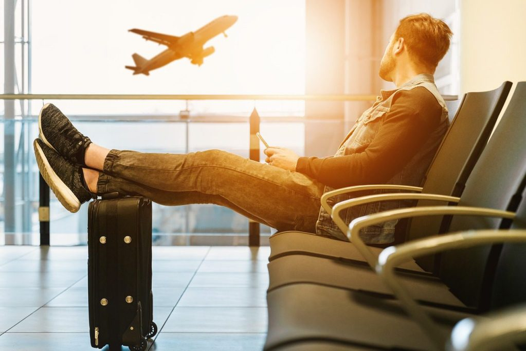 man looking at plane with feet on suitcase
