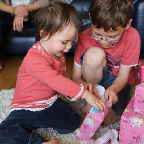 Isaac helping Kara unwrap her presents
