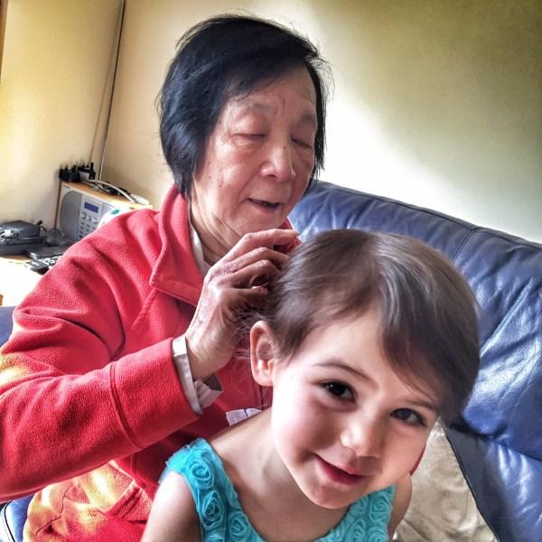 Grandma brushing Kara's hair