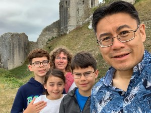 A family of five posing for a selfie at Corfe Castle