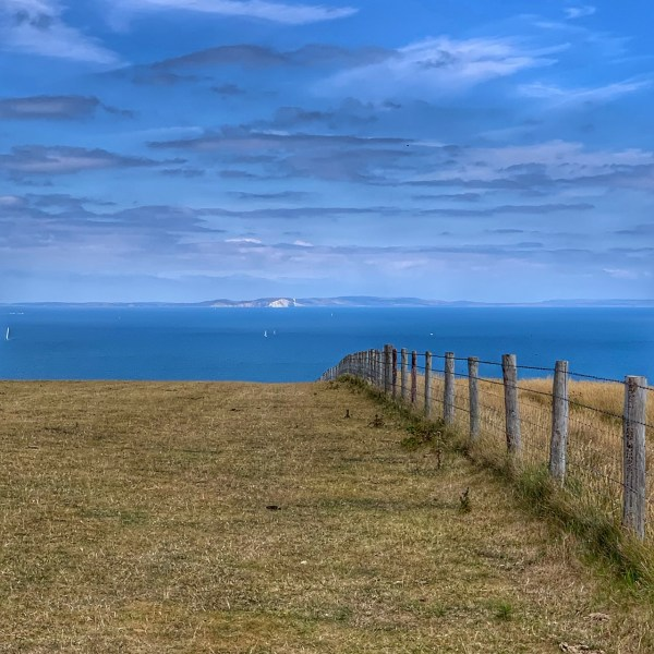 grassy hilltop path looking out to the Isle of Wight