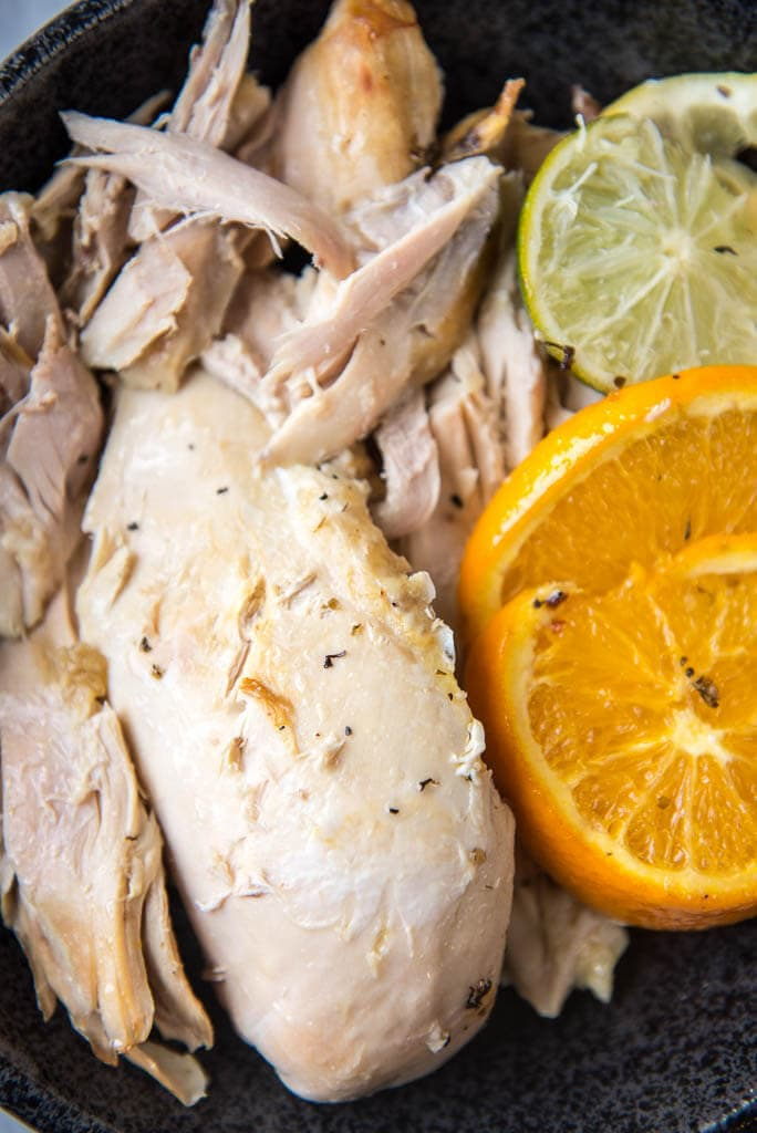 Shredded slow cooker whole chicken with lemon and lime slices on the side, placed on a black plate.