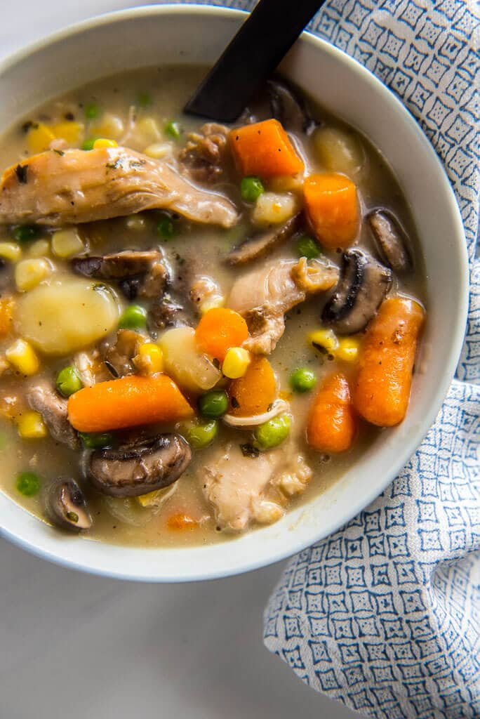 slow cooker chicken and dumplings in white bowl with white and blue napkin