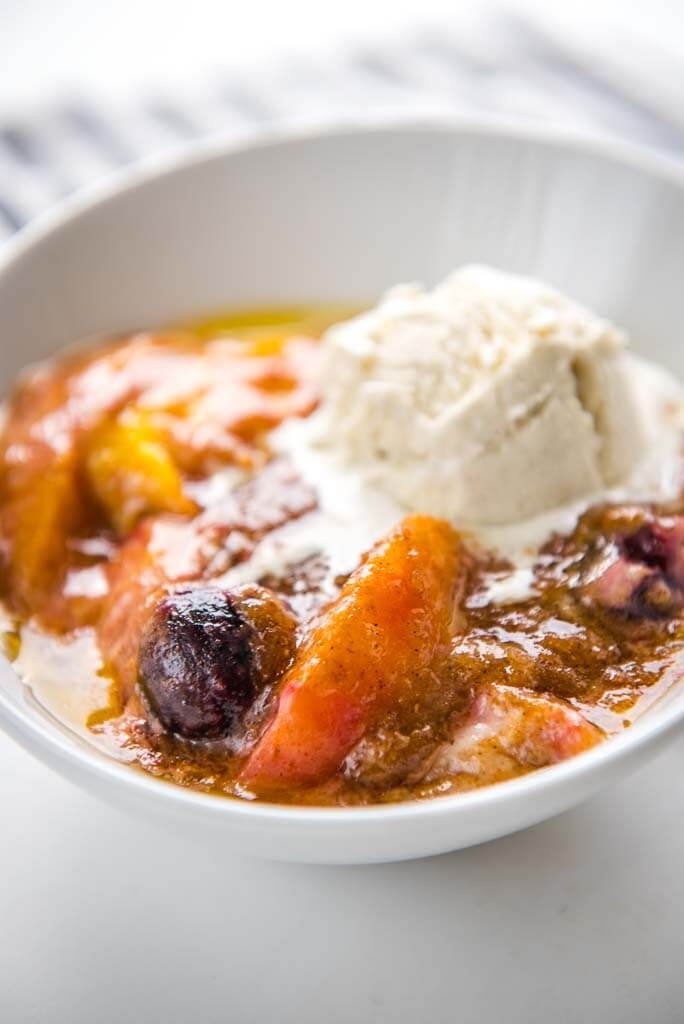 slow cooker peach and cherry cobbler in white bowl