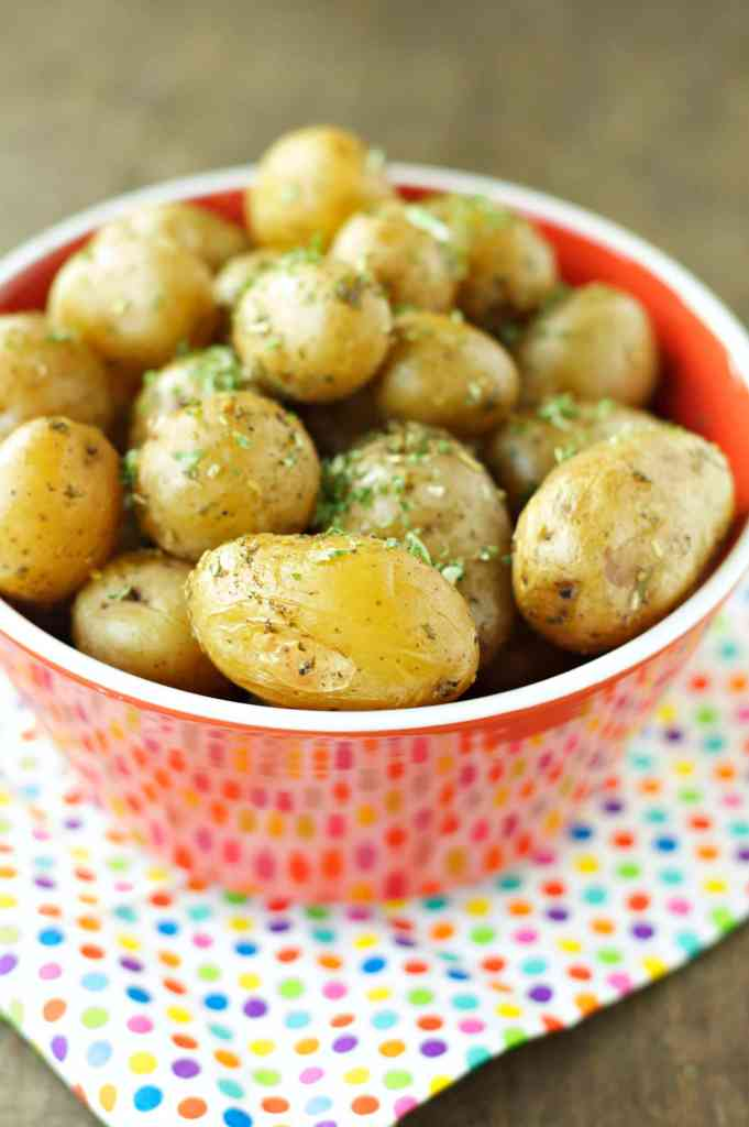 Slow Cooker Herbed Baby Potatoes in a red bowl with a festive polka dot napkin