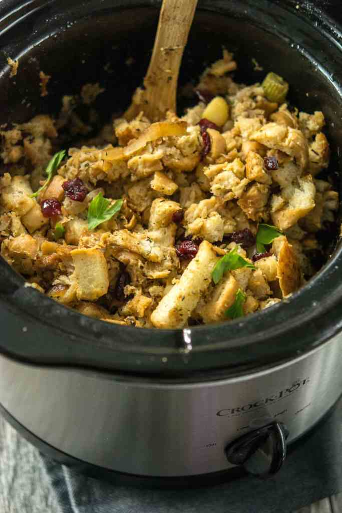 Slow Cooker Stuffing with Caramelized Apple and dried cranberries in round slow cooker with wooden spoon