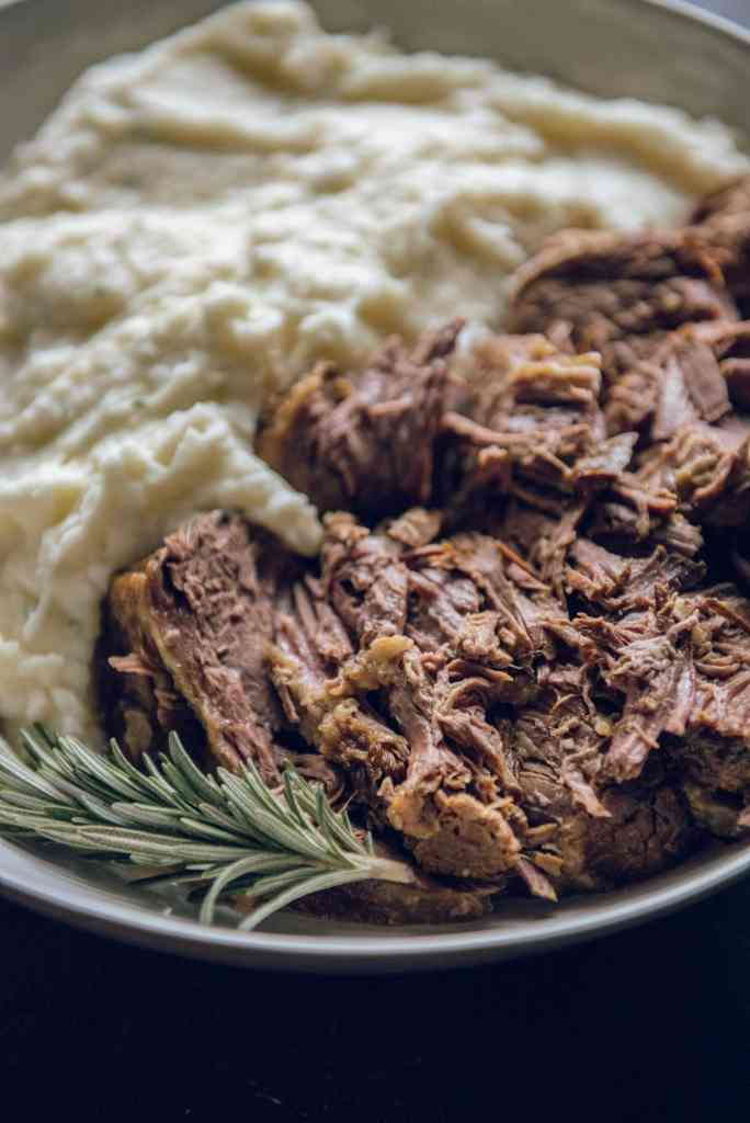 Roast Beef in a white bowl with mashed potatoes and a sprig of rosemary