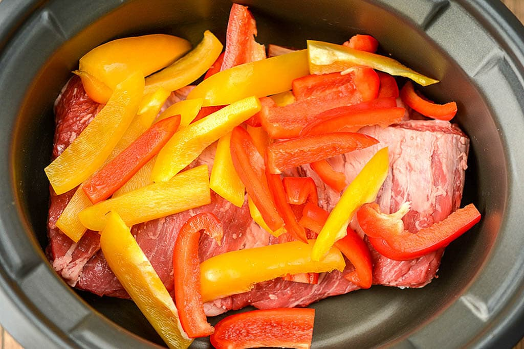 Sliced bell peppers on top of skirt steak - Slow Cooker Steak Fajitas