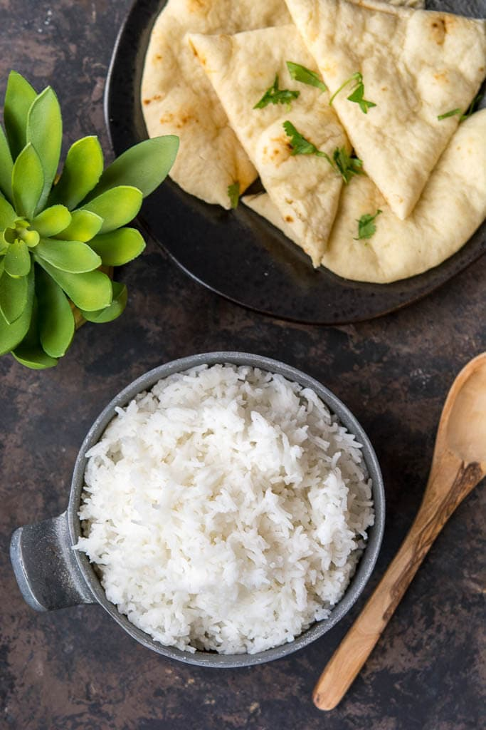 overhead shot of basmati rice and naan with a succulent and wooden spoon