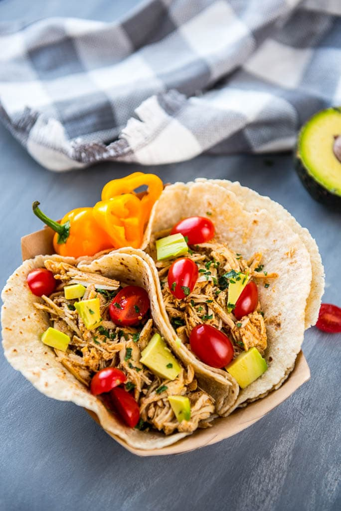 Easiest Slow Cooker Verde Chicken Tacos with toppings, gray and white checked napkin and avocado in the background.
