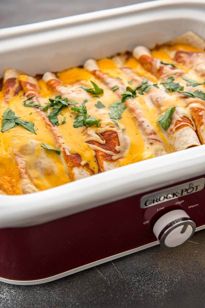 slow cooker enchiladas topped with melted cheese in casserole slow cooker