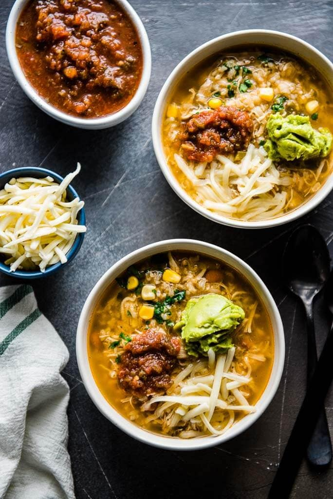 chipotle chicken burrito bowl soup in white bowls with a bowl of salsa and cheese