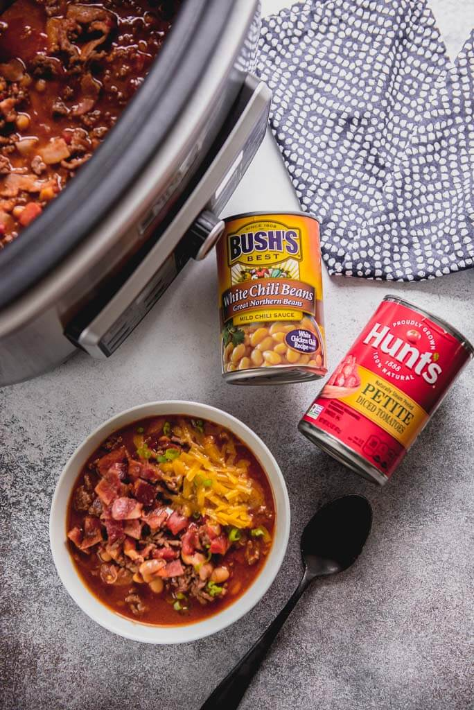 slow cooker maple bacon chili topped with cheese and green onions with a can of beans and a can of tomatoes