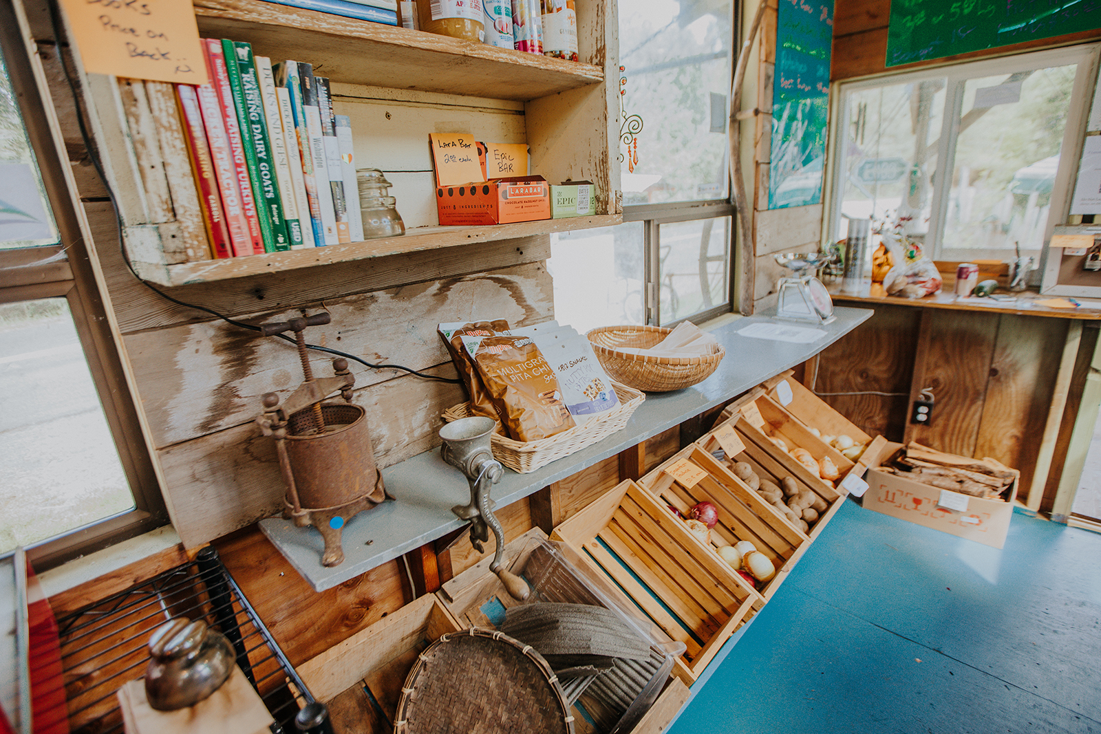Dried goods, books and produce rest on the shelves of the farm stand.