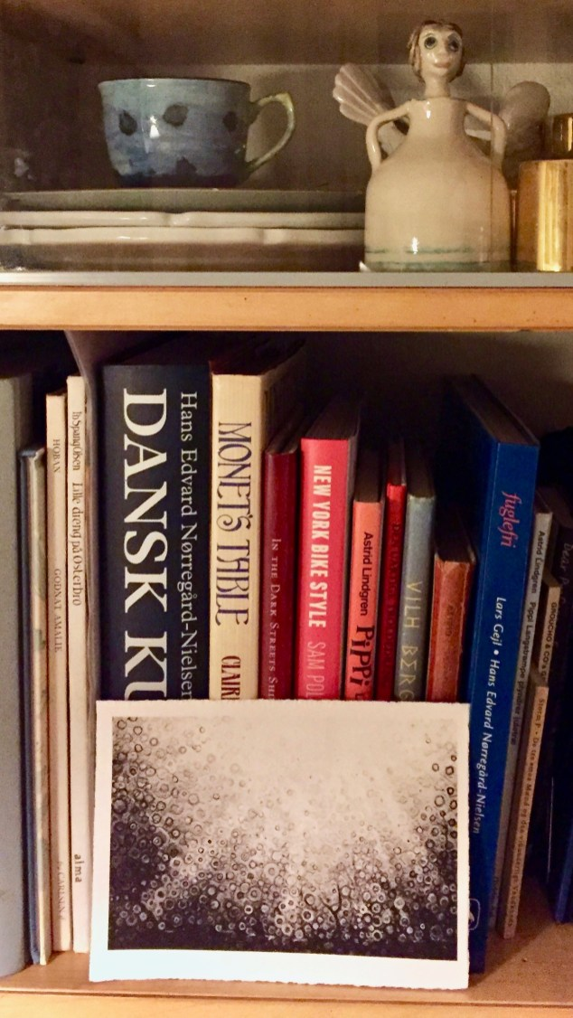 A postcard print gets cozy on a Danish bookshelf
