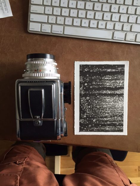 Black, white, and silver 'Wisdom' postcard print by Randall Stoltzfus on desk beside Hasselblad camera and computer keyboard