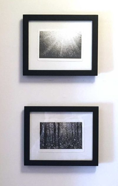 Two small monochrome postcard prints by Randall Stoltzfus framed and hanging on the wall