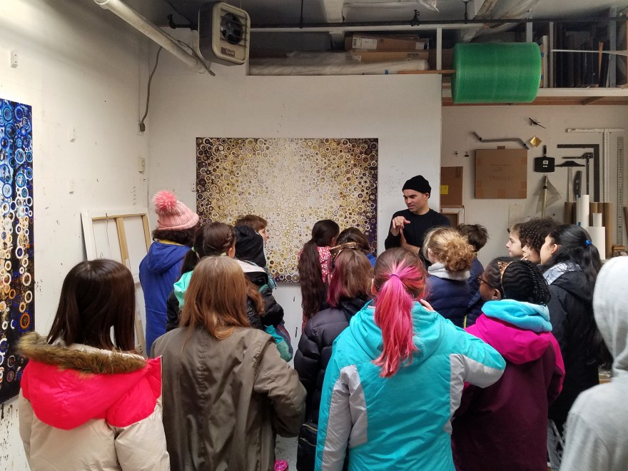 A class of sixth-grade students look at paintings with Randall Stoltzfus in his studio