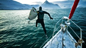 a surfer jumping in the ocean fro a boat