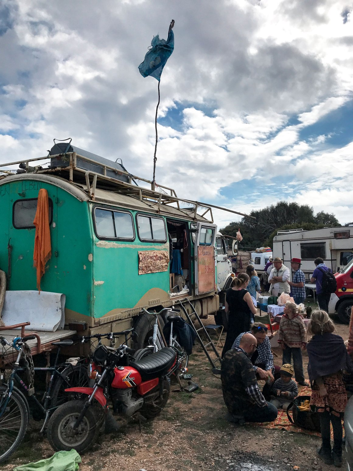 people at a flea market with green camper van and a motocycle