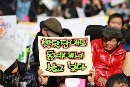 2012년 2월 22일에 열린 집회에서 참가자가 발달장애인도 동네에서 살고 싶다고 적힌 피켓을 들고 있다. (출처: 비마이너)