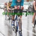 Photo of 2013 Ironman 70.3 World Championship competitor Alisha Kern riding her bike on rain-slick roads.