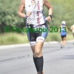 Photo of 2013 Ironman 70.3 World Championship competitor Edie Cox smiling broadly while on the run course.