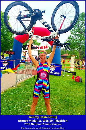 Color photo of triathlete Tammy Hassenpflug holding her bike over her head