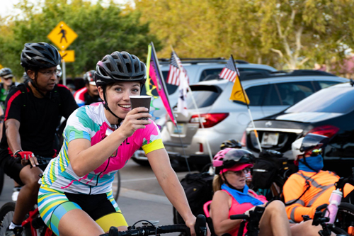 female cyclist with coffee cup in hand