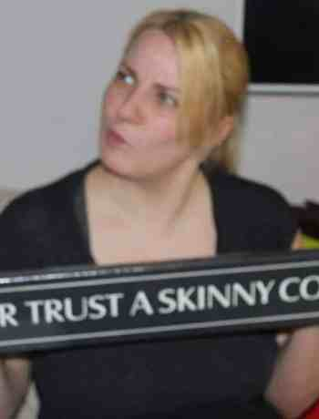 Betty holding a 'never trust a skinny chef' sign