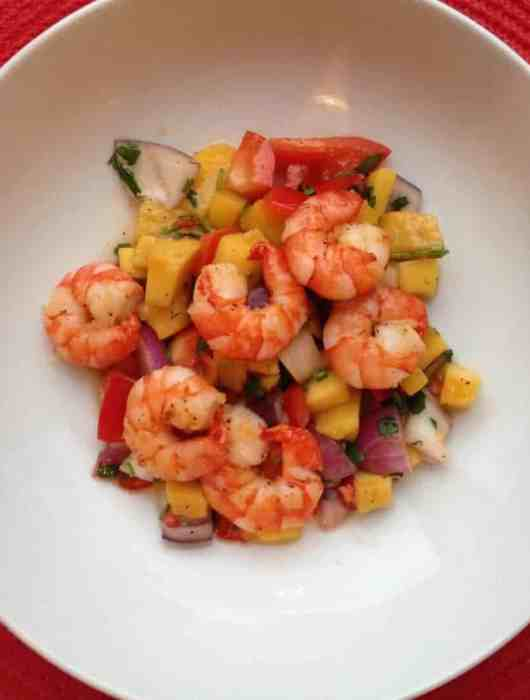 Pan fried prawns on a spicy mango salsa served in a large white bowl