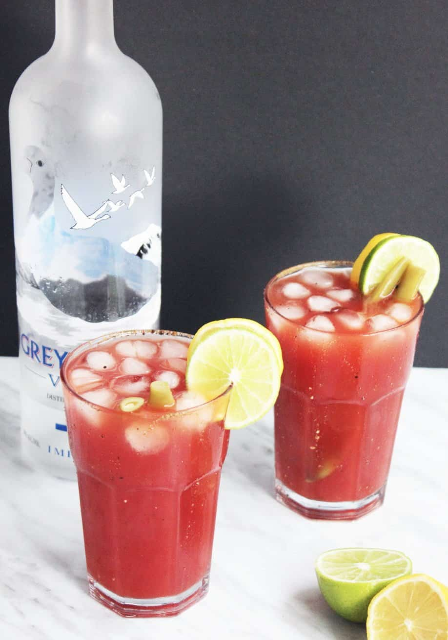 Two caesar drinks with lemon and lime garnish.