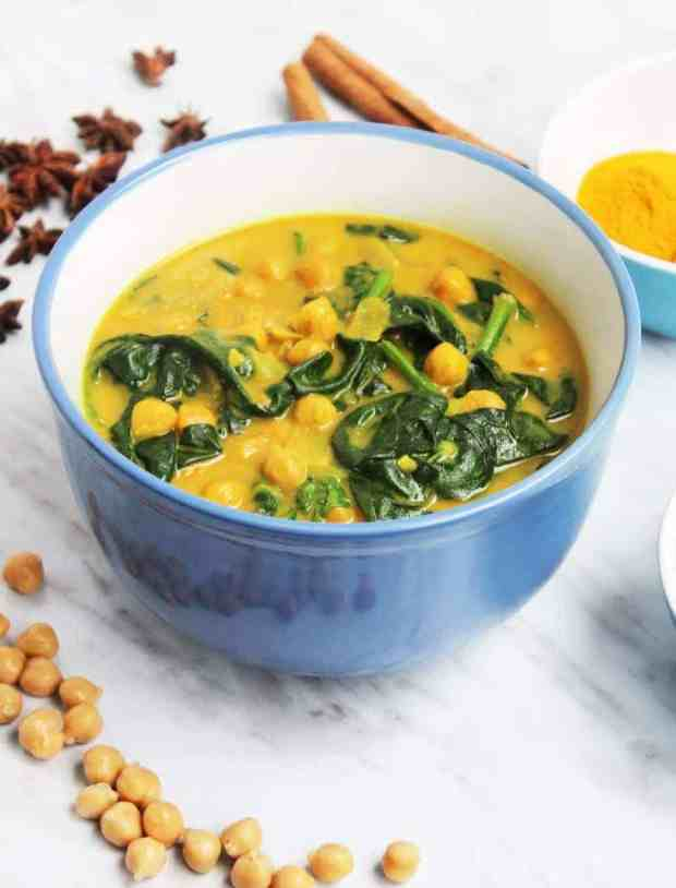 A big bowl of chickpea & spinach curry on a white marble tabletop, styled with the ingredients used in the dish