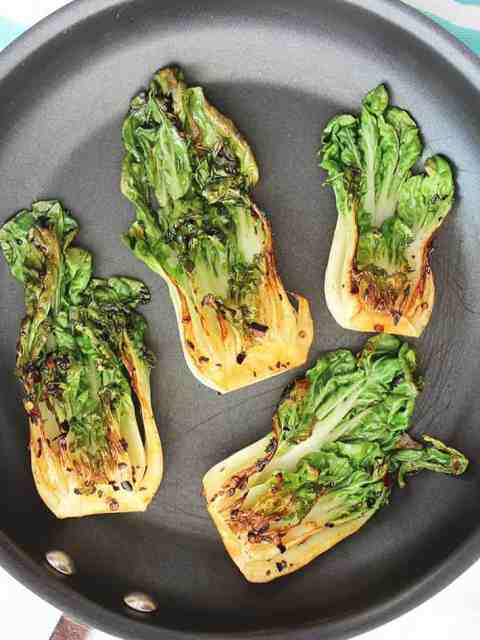 Four pak choi halves in a black frying pan