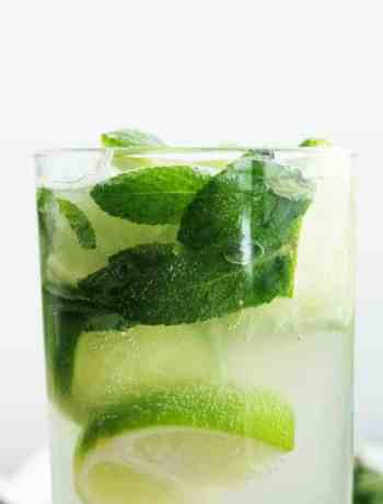 A closeup of a mojito elderflower cocktail on a white background
