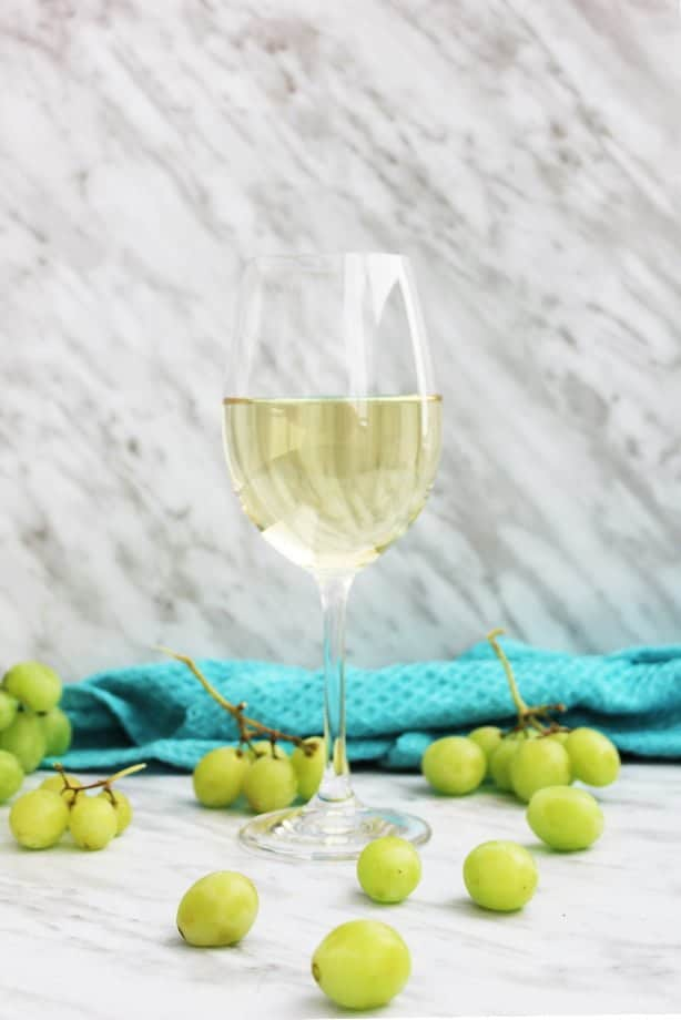 A glass of white wine with white grapes scattered around