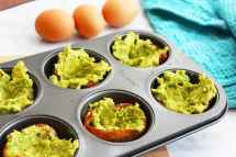 avocado spooned into cooked bacon in a muffin tin