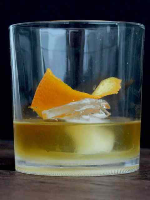 Close up of a smokey old fashioned in a whisky glass