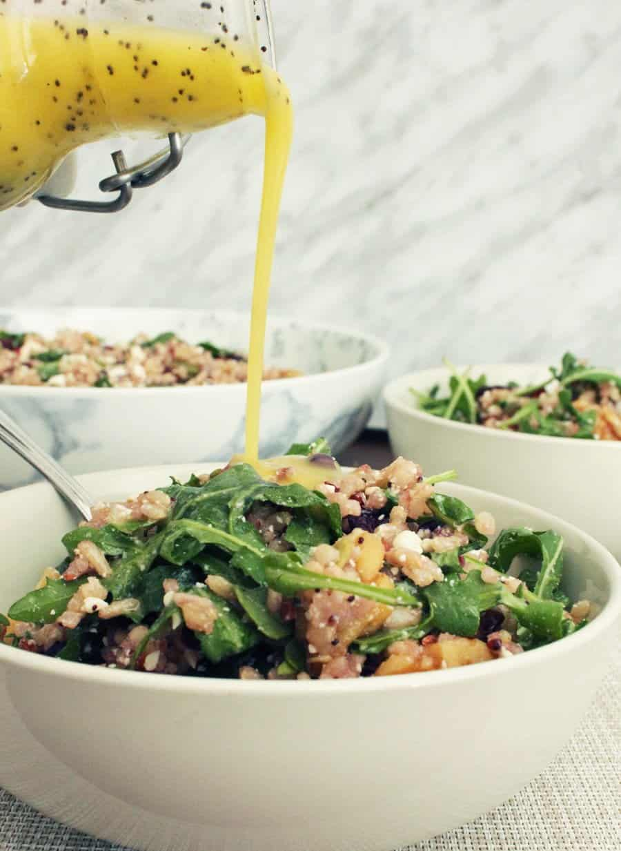Poppy seed dressing being pored over a small bowl of brown rice salad