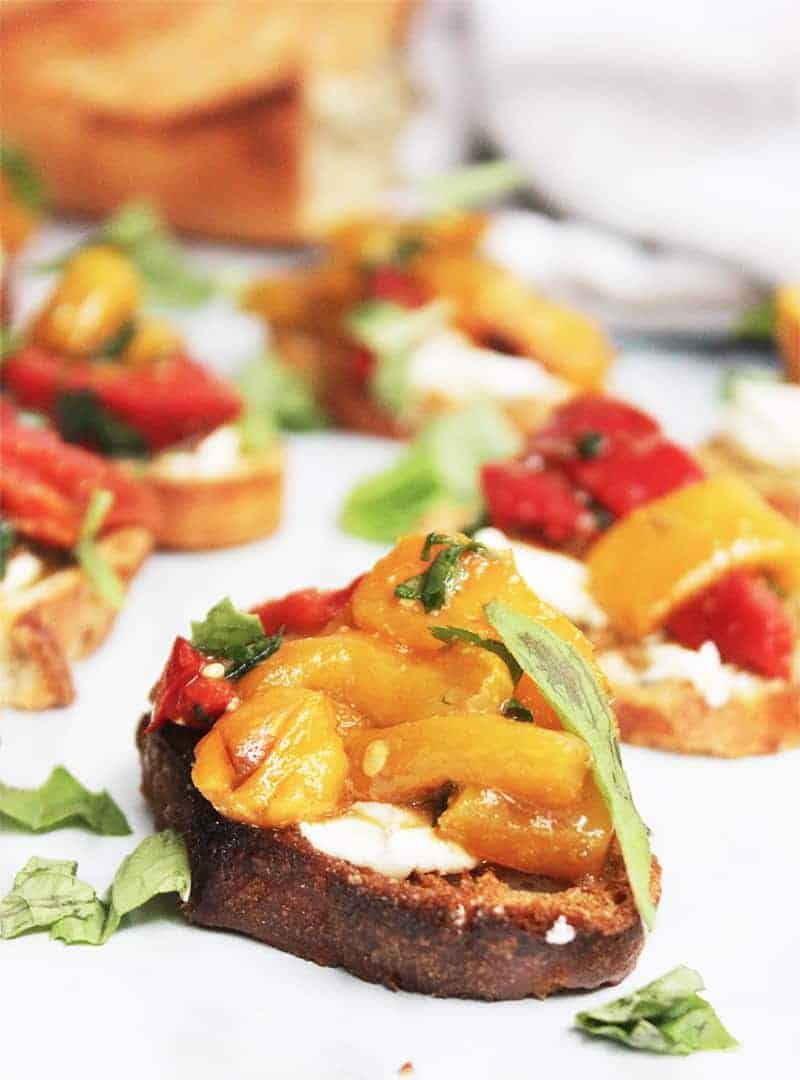 Close up of a topped crostini canape on a white work surface