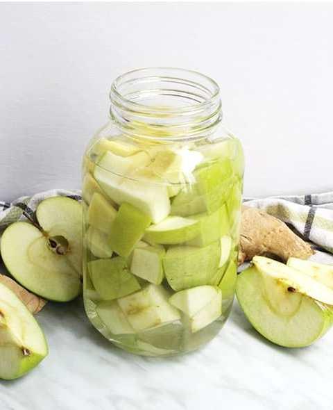 Green Apple Vodka in a jar next to sliced apples
