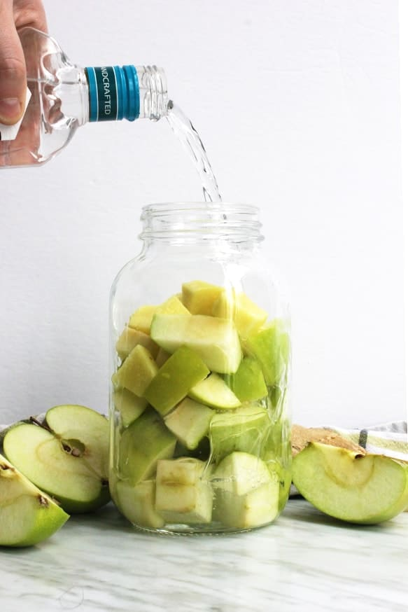 Vodka being poured over green apples